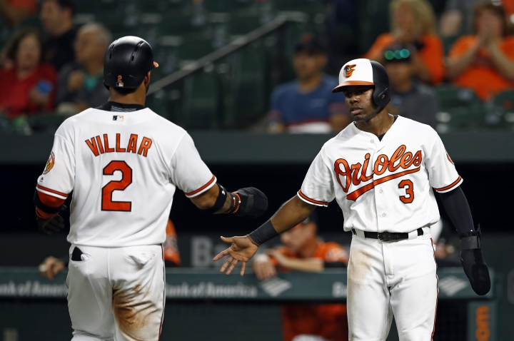 Baltimore Orioles' Cedric Mullins, right, greets teammate Jonathan Villar after they both scored on Tim Beckham's single in the first inning of a baseball game against the Oakland Athletics, Thursday, Sept. 13, 2018, in Baltimore. (AP Photo/Patrick Semansky)