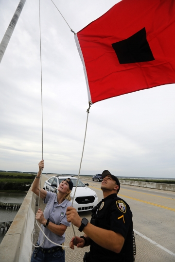 Isle of Palms Fire Chief Ann Graham, at left, and Isle of Palms police officer Thomas Molino III raise a tropical storm warning flag over the Isle of Palms Connector shortly after Charleston County, S.C., went under a tropical storm warning due to Hurricane Florence Thursday, Sept. 13, 2018, in Isle of Palms, S.C. (AP Photo/Mic Smith)