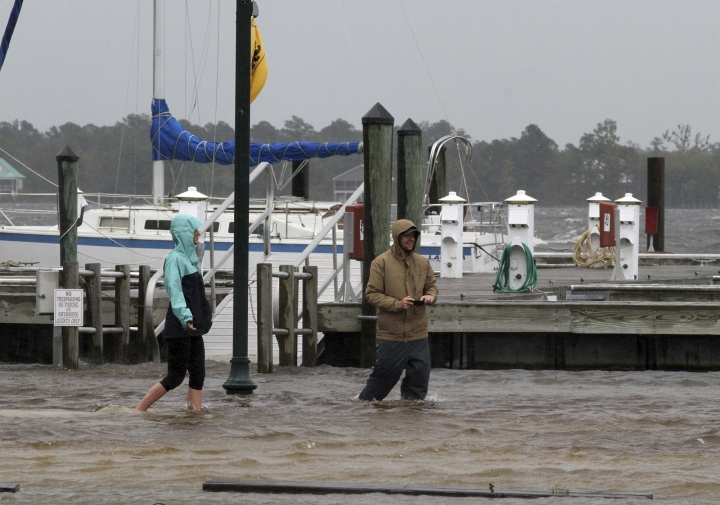 Jamie Thompson and Ryan Thompson walk through flooded areas along the Neuse River near East Front Street in New Bern, N.C. Thursday, Sept. 13, 2018. Hurricane Florence already has inundated coastal streets with ocean water and left tens of thousands without power, and more is to come. (Gray Whitley/Sun Journal via AP)