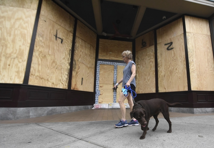 Deborah Covington walks his dog past Front Street Brewery in downtown Wilmington, N.C., Thursday, Sept. 13, 2018 ahead of Hurricane Florence. (Matt Born/The Star-News via AP)