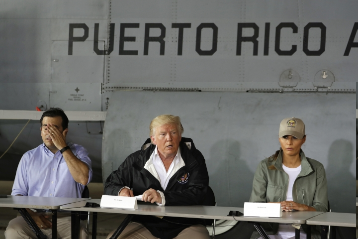 FILE - In this Oct. 3, 2017, file photo, President Donald Trump talks about recovery efforts after he and first lady Melania Trump arrived at Luis Muniz Air National Guard Base to survey hurricane damage in San Juan, Puerto Rico, as Puerto Rico Gov. Ricardo Rosselló, left, listens. Trump loves to cite stats, numbers to bolster his political standing. He just doesn't seem to care much about whether they're true. (AP Photo/Evan Vucci, File)