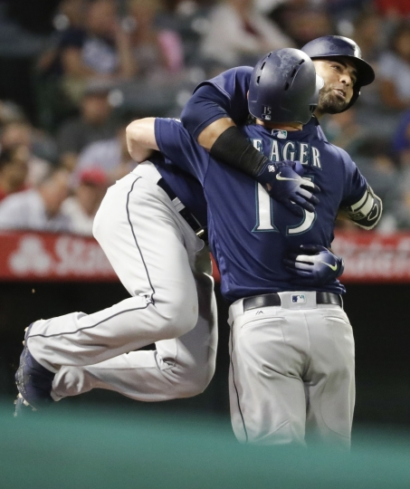 Seattle Mariners' Nelson Cruz, left, celebrates after his three-run home run with Mitch Haniger during the fourth inning of a baseball game against the Los Angeles Angels in Anaheim, Calif., Thursday, Sept. 13, 2018. (AP Photo/Chris Carlson)