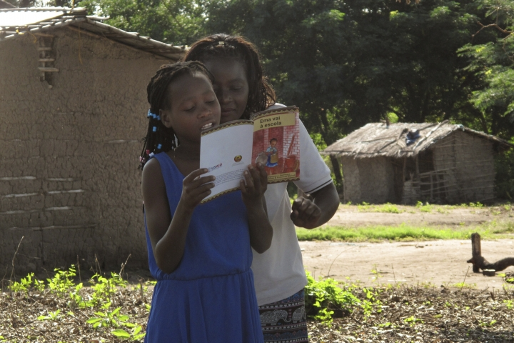 In this photo taken Friday April 20, 2018 in the Gorongosa National Park, a Mozambican girl reads as part of a program that aims to help girls stay in school longer and stay out of child marriage, a longstanding problem in the southern African country. The program consists of about 50 girls' clubs set up by the managers of Gorongosa National Park, who believe that human development and conservation go hand in hand. (AP Photo/Christopher Torchia)