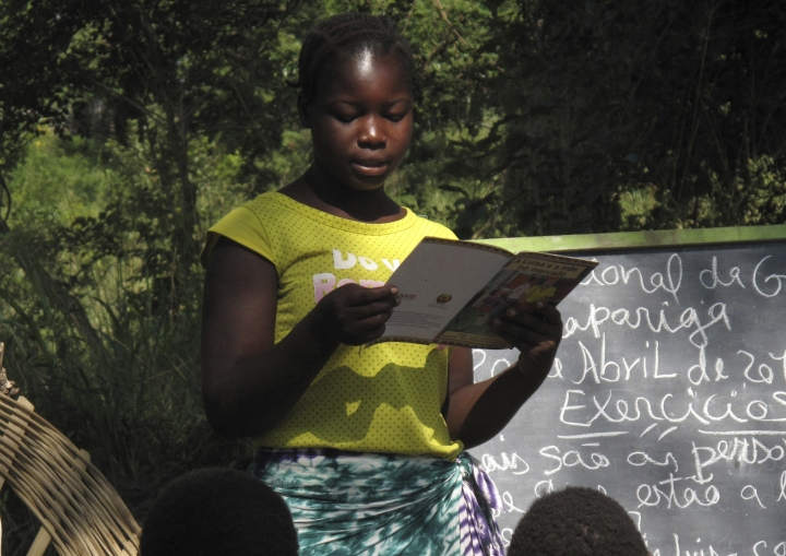 In this photo taken Friday, March 20, 2018 in the Gorongosa National Park, Mozambique, a Mozambican girl reads as part of a program that aims to help girls stay in school longer and stay out of child marriage, a longstanding problem in the southern African country. The program consists of about 50 girls' clubs set up by the managers of Gorongosa National Park, who believe that human development and conservation go hand in hand. (AP Photo/Christopher Torchia)