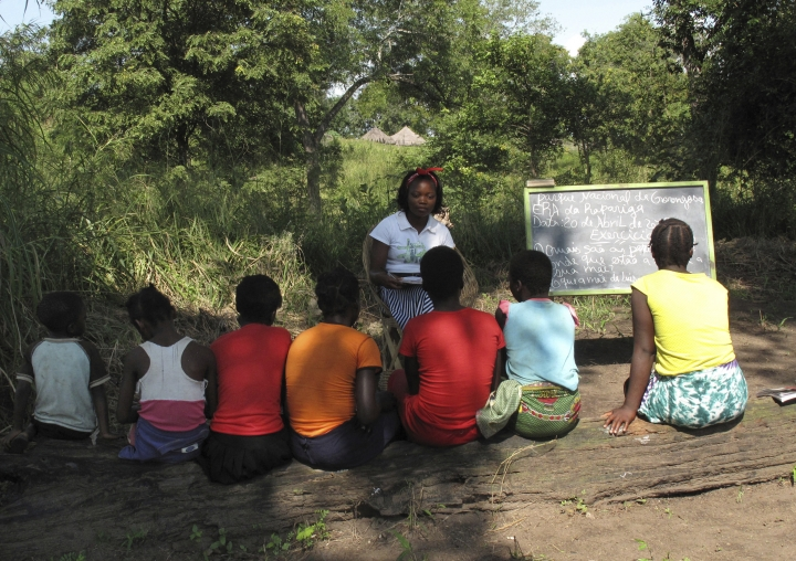 In this photo taken Friday April 20, 2018 in the Gorongosa National Park, Mozambique, Mozambican girls take part in a lesson as part of a program that aims to help girls stay in school longer and stay out of child marriage, a longstanding problem in the southern African country. The program consists of about 50 girls' clubs set up by the managers of Gorongosa National Park, who believe that human development and conservation go hand in hand. (AP Photo/Christopher Torchia)