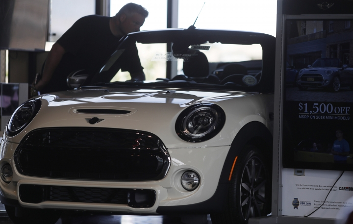 In this Thursday, Aug. 30, 2018, photo, a prospective buyer looks over a 2019 Cooper S convertible on the showroom floor of a Mini dealership in Highlands Ranch, Colo. On Friday, Sept. 14, the Commerce Department releases U.S. retail sales data for August. (AP Photo/David Zalubowski)