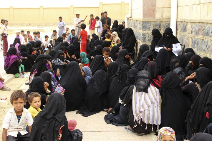 In this Aug. 25, 2018 photo, women wait with their children in front of the Aslam Health Center, in Hajjah, Yemen. Yemenis in the isolated pocket in the north have been reduced to eating boiled leaves from a local vine to stave off starvation, with no aid reaching many families who need it most. The situation in Aslam district is a sign of the holes in an international aid system that is already overwhelmed but is the only thing standing between Yemen's people and massive death from starvation amid the country's 3-year civil war. (AP Photo/Hammadi Issa)
