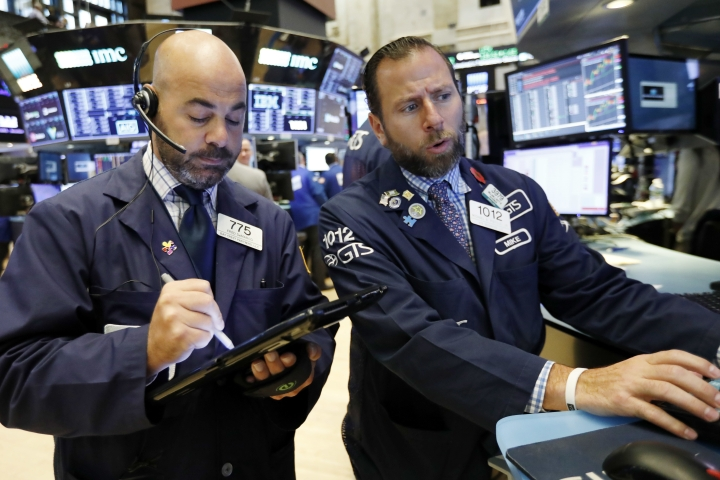 Trader Fred DeMarco, left, and specialist Michael Pistillo work on the floor of the New York Stock Exchange, Friday, Sept. 14, 2018. U.S. stocks are little changed Friday morning as banks climb but retailers and big-dividend stocks slide. (AP Photo/Richard Drew)