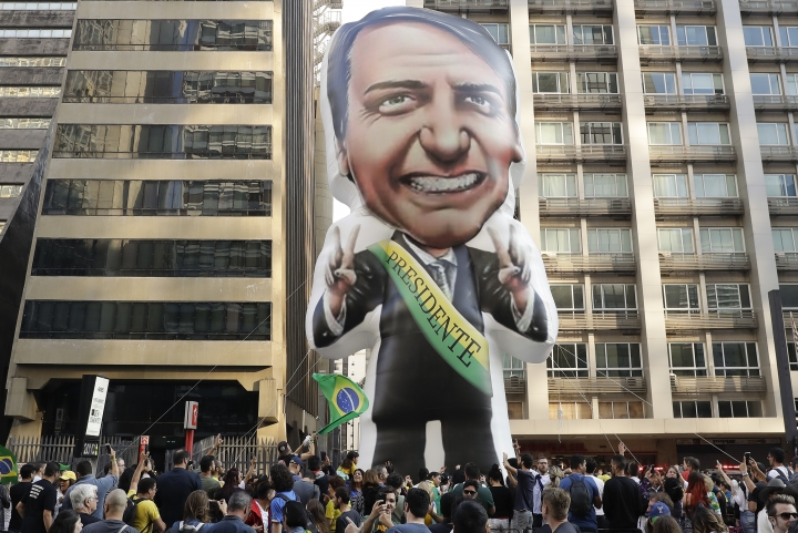 """FILE - In this Sept. 9, 2018 file photo, supporters of Jair Bolsonaro, presidential candidate for the National Social Liberal Party who was stabbed during a campaign event days ago, exhibit a large, inflatable doll in his image to show support for him, in Sao Paulo, Brazil. Silas Malafaia, one of Brazil's most influential pastors, visited Bolsonaro in the hospital. """"God is an expert in turning chaos into a blessing,"""" Malafaia said in a video he posted on YouTube from Bolsonaro's hospital room. (AP Photo/Andre Penner, File)"""
