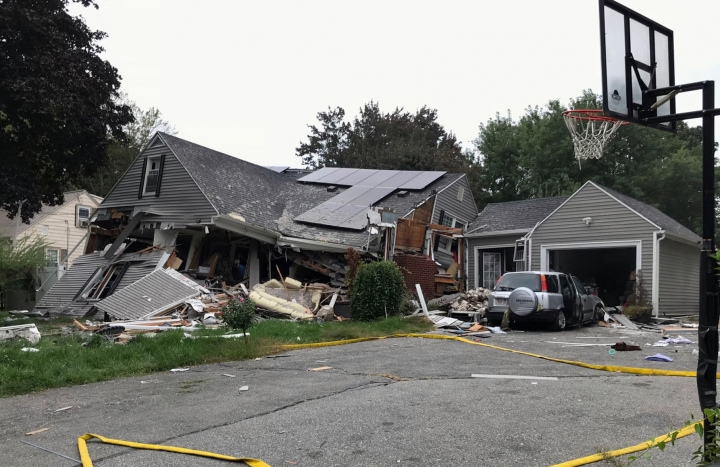 ADDS IDENITY OF VICTIM LEONEL RONDON- A collapsed home and car sit damaged on Chickering Street in Lawrence, Mass., Thursday, Sept. 13, 2018, after a series of gas explosions in several communities north of Boston. Authorities said Leonel Rondon died after the chimney toppled by the exploding house crashed into his car in the driveway. He was rushed to a Boston hospital but pronounced dead there in the evening. (Carl Russo/The Eagle-Tribune via AP)