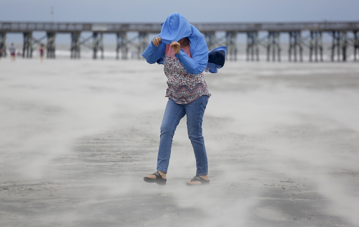 Marian Rivera covers her face from the strong wind and blowing sand as Tropical Storm Florence approaches the Isle of Palms, S.C., Friday, Sept. 14, 2018. (AP Photo/Mic Smith)