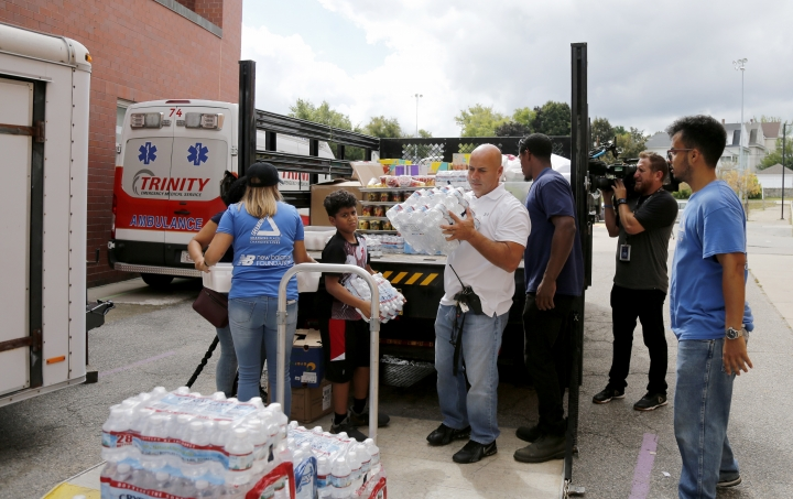 Volunteers help to unload a truck of donations outside the Parthum School in Lawrence, Mass., Friday, Sept. 14, 2018. Multiple houses were damaged Thursday afternoon from gas explosions and fires triggered by a problem with a gas line that feeds homes in several communities north of Boston. (AP Photo/(AP Photo/Mary Schwalm)