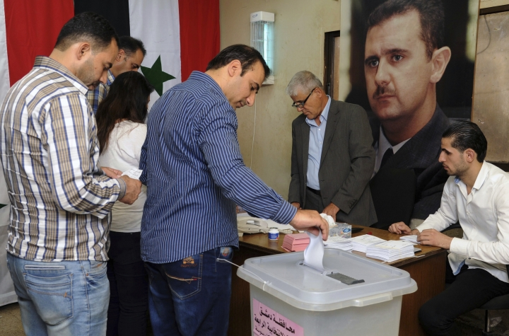 In this photo released by the Syrian official news agency SANA, Syrians cast their votes at a polling station during municipal elections, in Damascus, Syria, Sunday, Sept 16, 2018. Syria is holding its first municipal elections since 2011 amid tensions with the country's self-administered Kurdish region, which is refusing to allow polls. (SANA via AP)