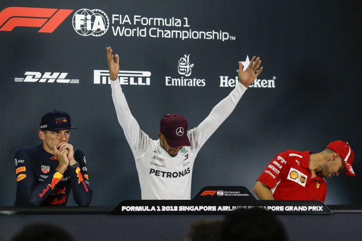 Mercedes driver Lewis Hamilton, center, of Britain reacts during a press conference following his Singapore Formula One Grand Prix win at the Marina Bay City Circuit in Singapore, Sunday, Sept. 16, 2018. Max Verstappen of Netherlands, left, and Sebastian Vettel of Germany, right. (AP Photo/Yong Teck Lim)