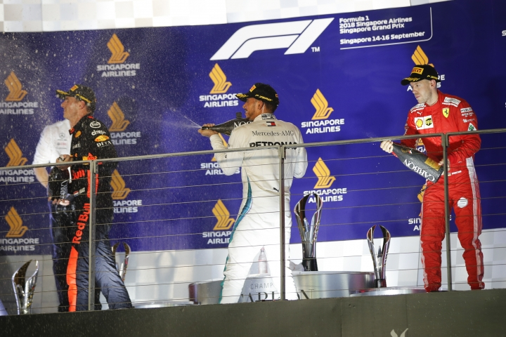 Mercedes driver Lewis Hamilton of Britain, center, sprays champagne at Red Bull Racing driver Max Verstappen of Netherlands, left, as he celebrates after winning the Singapore Formula One Grand Prix, next to Ferrari driver Sebastian Vettel of Germany, at the Marina Bay City Circuit in Singapore, Sunday, Sept. 16, 2018. (AP Photo/Vincent Thian)