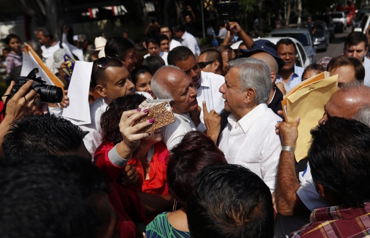 Mexican President-elect Andres Manuel Lopez Obrador talks with people during an event in Tepic, Mexico, Sunday, Sept. 16, 2018. Lopez Obrador kicked off his nationwide tour with a new security group of 20 people who will rotate five at a time to accompany him everywhere, with the goal of allowing the incoming president to interact with voters without getting squashed. (AP Photo/Eduardo Verdugo)