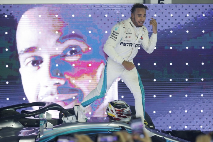 Mercedes driver Lewis Hamilton of Britain celebrates on his car after winning the Singapore Formula One Grand Prix at the Marina Bay City Circuit in Singapore, Sunday, Sept. 16, 2018. (AP Photo/Vincent Thian)