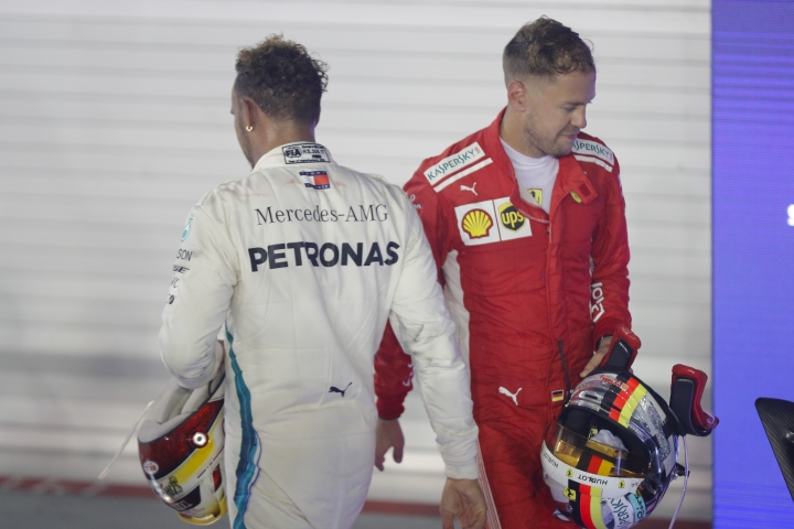 Third place Ferrari driver Sebastian Vettel of Germany, right, walks past race winner Mercedes driver Lewis Hamilton of Britain during the Singapore Formula One Grand Prix at the Marina Bay City Circuit in Singapore, Sunday, Sept. 16, 2018. (AP Photo/Vincent Thian)
