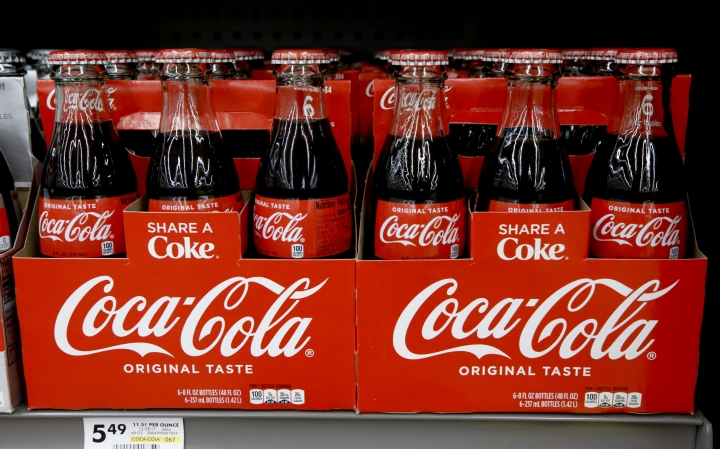 "FILE--In this Aug. 8, 2018, file photo, bottles of Coca Cola sit on a shelf in a market in Pittsburgh. The Coca-Cola Company says that it's ""closely watching"" the growth of the use of a non-psychoactive element of cannabis in wellness drinks. (AP Photo/Gene J. Puskar, file)"