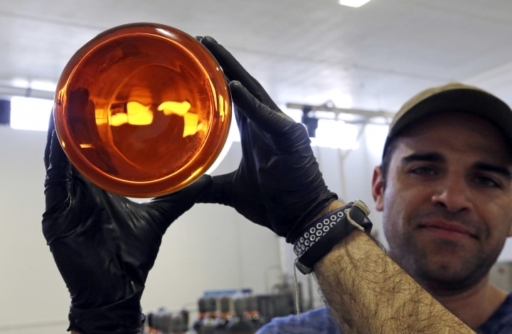 """FILE--In this April 24, 2018, file photo, Julian Cabrera, factory manager at New Earth Biosciences, holds up a large glass beaker containing thick, golden-colored, fully-refined CBD oil in Salem, Ore. The Coca-Cola Company says that it's """"closely watching"""" the growth of the use of the non-psychoactive element of cannabis in wellness drinks. (AP Photo/Don Ryan, file)"""