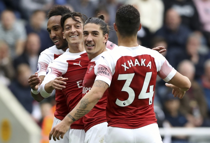 Arsenal's Mesut Ozil, centre, celebrates scoring his side's second goal of the game with teammates, during the English Premier League soccer match between Newcastle United and Arsenal at St James' Park, in Newcastle, England, Saturday, Sept. 15, 2018. (Owen Humphreys/PA via AP)