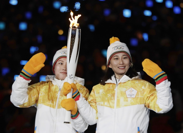 """FIEL - In this Feb. 9, 2018, file photo, North Korea's Jong Su Hyon, left, and South Korea's Park Jong-ah carry the torch in the stadium during the opening ceremony of the 2018 Winter Olympics in Pyeongchang, South Korea. South Korean President Moon Jae-in heads to his meeting with North Korea's leader with a huge civilian entourage including the third-generation heir of South Korea's largest business group and a Colorado-born pop diva nicknamed the """"Korean Beyonce."""" Park is also included in the South Korean delegation. (AP Photo/Petr David Josek, File)"""