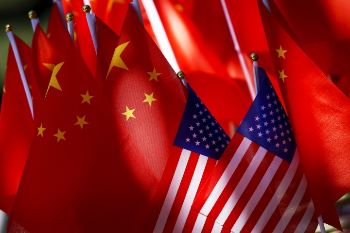 "In this Sept. 16, 2018, photo, American flags are displayed together with Chinese flags on top of a trishaw in Beijing. The American Chamber of Commerce in China says Beijing will ""dig its heels in"" after U.S. tariff hikes and appealed for a negotiated end to their trade battle. The chamber on Tuesday, Sept. 18 warned a ""downward spiral"" appears certain after President Donald Trump approved a tariff hike on $200 billion of Chinese imports in a dispute over Beijing's technology policy. (AP Photo/Andy Wong)"