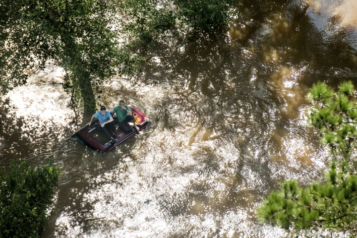 Two people sit on the roof of a vehicle in floodwaters after Hurricane Florence struck the Carolinas, Monday, Sept. 17, 2018, near Wallace, S.C. (AP Photo/Sean Rayford)