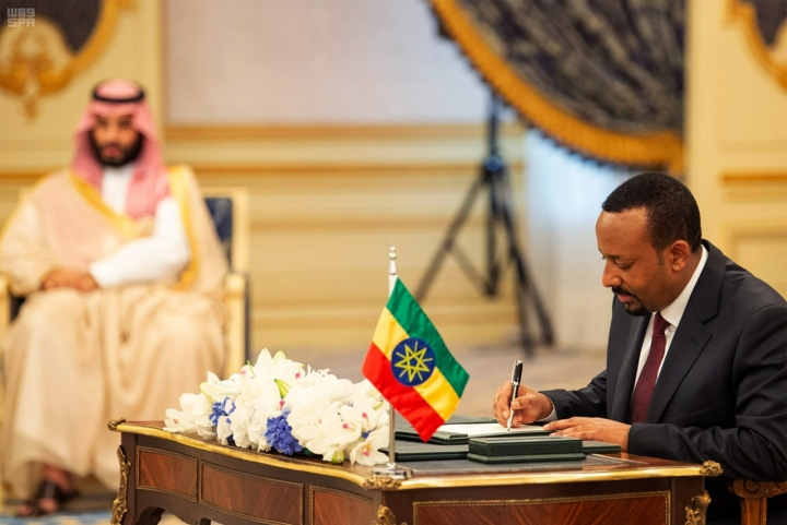 In this photograph released by the state-run Saudi Press Agency, Ethiopian Prime Minister Abiy Ahmed, right, signs a peace accord with Eritrea as Saudi Crown Prince Mohammed bin Salman looks on in the distance in Jiddah, Saudi Arabia on Sunday, Sept. 16, 2018. The leaders of Ethiopia and Eritrea were in Saudi Arabia on Sunday to sign a peace accord between the two East African nations. (Saudi Press Agency via AP)