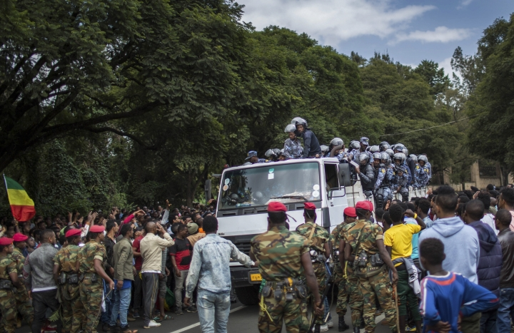Members of the army and riot police attempt to control protestors from the capital and those displaced by ethnic-based violence over the weekend in Burayu, as they demonstrate to demand justice from the government in Addis Ababa, Ethiopia Monday, Sept. 17, 2018. Several thousand Ethiopians have gone out onto the streets of the capital to protest ethnic-based attacks in the outskirts of the city in which more than 20 people died over the weekend. (AP Photo/Mulugeta Ayene)