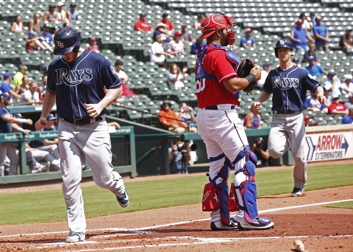 Tampa Bay Rays C.J. Cron, left, and Joey Wendle, score as Texas Rangers catcher Carlos Perez (60) stand by home plate during the second inning of a baseball game Wednesday, Sept. 19, 2018, in Arlington, Texas. (AP Photo/Mike Stone)