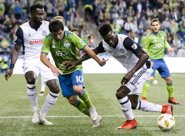 Seattle Sounders midfielder Nicolas Lodeiro (10) loses the ball to Philadelphia Union forward C.J. Sapong on the edge of the box during the first half of an MLS soccer match Wednesday, Sept. 19, 2018, in Seattle. (Bettina Hansen/The Seattle Times via AP)