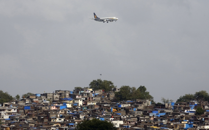 FILE - In this June 15, 2016 file photo, an aircraft of India's private airline Jet Airways flies above shanties adjacent to the Chhatrapati Shivaji airport as it prepares to land in Mumbai, India. A Jet Airways flight returned to Mumbai, India's financial capital, on Thursday, Sept. 20, 2018, after dozens of passengers complained of ear pain and nose bleeding due to the loss in cabin pressure. (AP Photo/ Rajanish Kakade, File)
