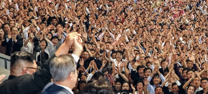 """In this Wednesday, Sept. 19, 2018, file photo, South Korean President Moon Jae-in, foreground right, and North Korean leader Kim Jong Un raise their hands after watching the mass games performance of """"The Glorious Country"""" at May Day Stadium in Pyongyang, North Korea. (Pyongyang Press Corps Pool via AP,c File)"""