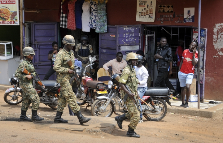 Ugandan soldiers patrol on the streets of the Kamwokya neighborhood where pop star-turned-opposition lawmaker Bobi Wine, whose real name is Kyagulanyi Ssentamu, has his recording studio and many supporters, in Kampala, Uganda Thursday, Sept. 20, 2018. Security forces took Bobi Wine into custody when he arrived from the United States on Thursday, angering his supporters, while authorities barred public gatherings. (AP Photo/Ronald Kabuubi)