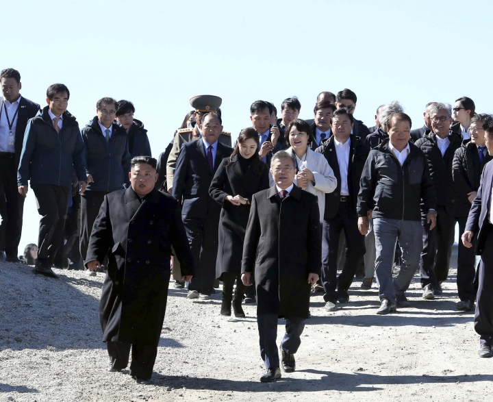 South Korean President Moon Jae-in, front right right, and North Korean leader Kim Jong Un visit Mount Paektu in North Korea, Thursday, Sept. 20, 2018. The two Korean leaders took to the road for the final day of their summit Thursday, heading to a beautiful volcano considered sacred in the North and used in its propaganda to legitimize the Kims' three generations of rule. (Pyongyang Press Corps Pool via AP)