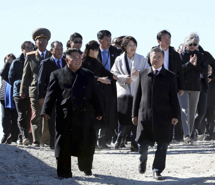 South Korean President Moon Jae-in, front right, and North Korean leader Kim Jong Un visit Mount Paektu in North Korea, Thursday, Sept. 20, 2018. The two Korean leaders took to the road for the final day of their summit Thursday, heading to a beautiful volcano considered sacred in the North and used in its propaganda to legitimize the Kims' three generations of rule. (Pyongyang Press Corps Pool via AP)
