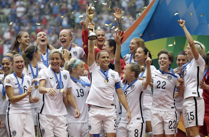 """FILE - In this, July 5, 2015 file photo, the United States Women's National Team celebrates with the trophy after they beat Japan 5-2 in the FIFA Women's World Cup soccer final in Vancouver, British Columbia, Canada. FIFA is making a concession to women's football and will start funding business-class flights for some 2019 Women's World Cup teams' travel to France. FIFA official Emily Shaw also tells a women's sports law conference total prize money will """"significantly increase"""" from $15 million shared among 24 teams at the 2015 edition. (AP Photo/Elaine Thompson, File)"""