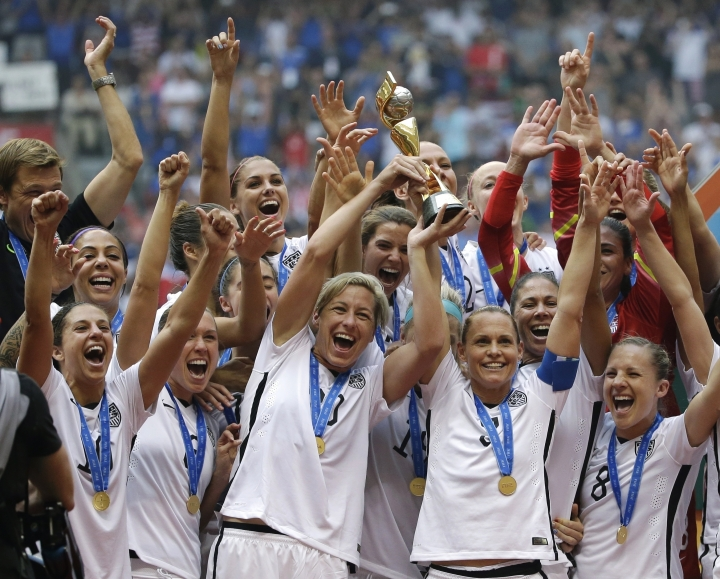 """FILE - In this July 5, 2015, file photo, the United States Women's National Team celebrates with the trophy after they beat Japan 5-2 in the FIFA Women's World Cup soccer championship in Vancouver, British Columbia, Canada. FIFA official Emily Shaw said Thursday, Sept. 20, 2018 at the Women In Sports Law conference that FIFA will start funding business-class flights for some of the Women's World Cup teams traveling to France for next year's tournament and that total prize money will also """"significantly increase"""" from the $15 million shared among 24 teams at the 2015 tournament. (AP Photo/Elaine Thompson, File)"""