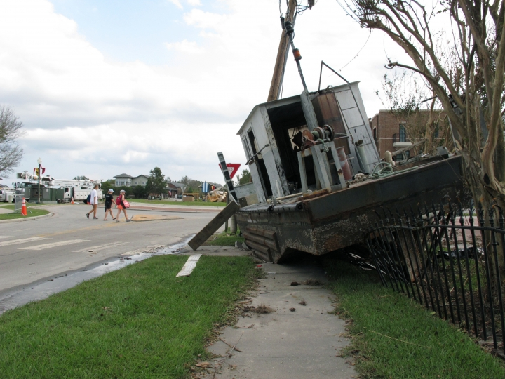 Women walk past a beached vessel on East Front Street in New Bern, N.C., on Thursday, Sept. 20, 2018. The craft was washed ashore in the city's historic district a week earlier by Hurricane Florence. (AP Photo/Allen G. Breed)