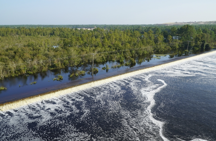 In this drone photo released by Duke Energy, flooding from the swollen Cape Fear River overtops an earthen dike at Sutton Lake, a 1,100-acre (445-hectare) lake at the L.V. Sutton Power Station near Wilmington, N.C. , Thursday, Sept. 20, 2018. Duke Energy activated a high-level emergency alert at the retired coal-fired power plant due to the flooding, raising concerns of a potential breach. (Duke Energy via AP)