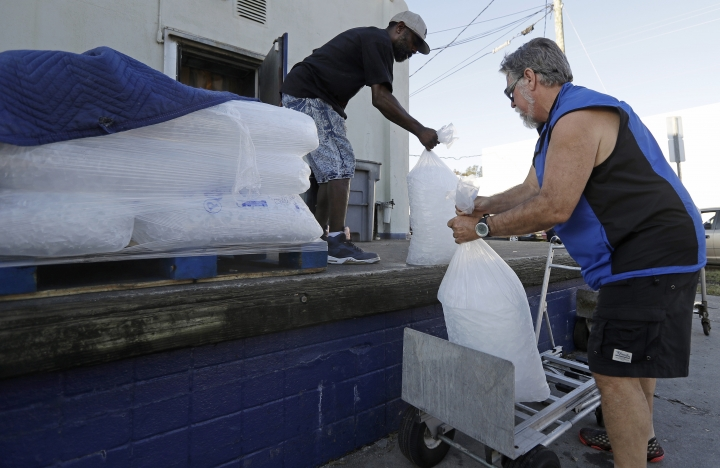 FILE - In this Sept. 19, 2018, file photo, Stan Atamanchuk, right, buys large bags of ice from Rose Ice & Coal days after Hurricane Florence in Wilmington, N.C. Many in Wilmington woke up Wednesday suddenly very tired. The days-long scavenger hunt for gas and ice was over as stores opened and relief agencies were able to roll into the city. (AP Photo/Chuck Burton, File)