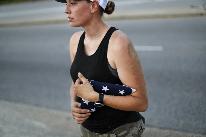 U.S. Army Sgt. Rose Stromberg holds the American flag she was able to retrieve from her storage unit which was flooded in the aftermath of Hurricane Florence in Spring Lake, N.C., Wednesday, Sept. 19, 2018. The flag, which is adorned with all the names of those killed in the 9/11 terrorist attacks, flew with her during her deployment in Afghanistan. (AP Photo/David Goldman)