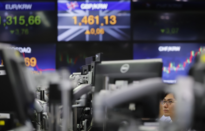 A currency trader works near screens showing the foreign exchange rate at the foreign exchange dealing room in Seoul, South Korea, Friday, Sept. 21, 2018. Asian stocks rose Friday after Wall Street hit a new high and a survey showed Japanese manufacturing accelerating. (AP Photo/Lee Jin-man)