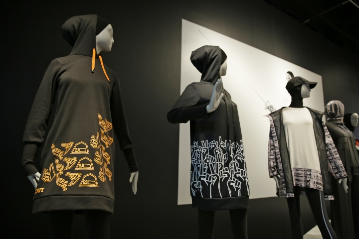 In this photo taken Thursday, Sept. 20, 2018, is a hooded knee-length dress at left made by Sarah Elenany for Muslim Girls, who wanted to participate in the Scout Association of the United Kingdom, in the exhibit Contemporary Muslim Fashions at the M. H. de Young Memorial Museum in San Francisco. The first major museum exhibition of contemporary Muslim women's fashion reflects designs from around the world that are vibrant and elegant, playful and diverse. The exhibit opens on Saturday. (AP Photo/Eric Risberg)