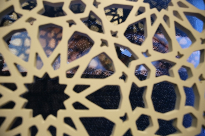 In this photo taken Thursday, Sept. 20, 2018, a photograph of a woman's eye is seen behind a latticework in the exhibit Contemporary Muslim Fashions at the M. H. de Young Memorial Museum in San Francisco. The first major museum exhibition of contemporary Muslim women's fashion reflects designs from around the world that are vibrant and elegant, playful and diverse. The show's creators hope the exhibit will show Muslim women as real people who can choose what they wear rather than as subjects ordered to cover their entire bodies or restricted in what they can wear. The exhibit opens on Saturday. (AP Photo/Eric Risberg)