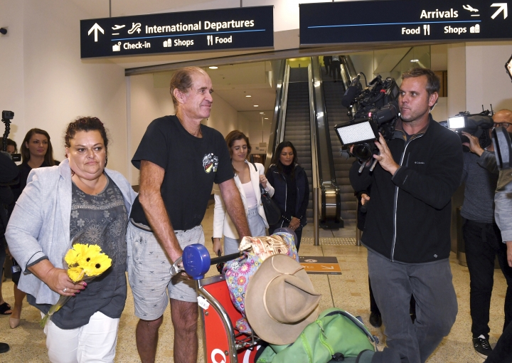 Australian filmmaker James Ricketson, third left, walks with his daughter Roxanne Holmes, second left, after his arrival at Sydney International Airport, Sunday, Sept. 23, 2018. Ricketson arrived two days after his 15-month stint in a Phnom Penh prison ended with clemency granted by Cambodian King Norodom Sihamoni. (Dean Lewins/AAP Image via AP)