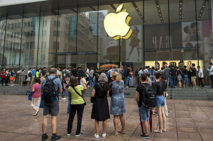 In this Friday, Sept. 21, 2018, photo, foreign tourists watch people queue in line to enter the Apple Store for the debut of the latest iPhones in Shanghai. China imposed new tariff hikes on U.S. goods on Monday, Sept. 24, 2018, and accused Washington of bullying, giving no sign of compromise in an intensifying battle over technology that is weighing on global economic growth. (Chinatopix via AP)