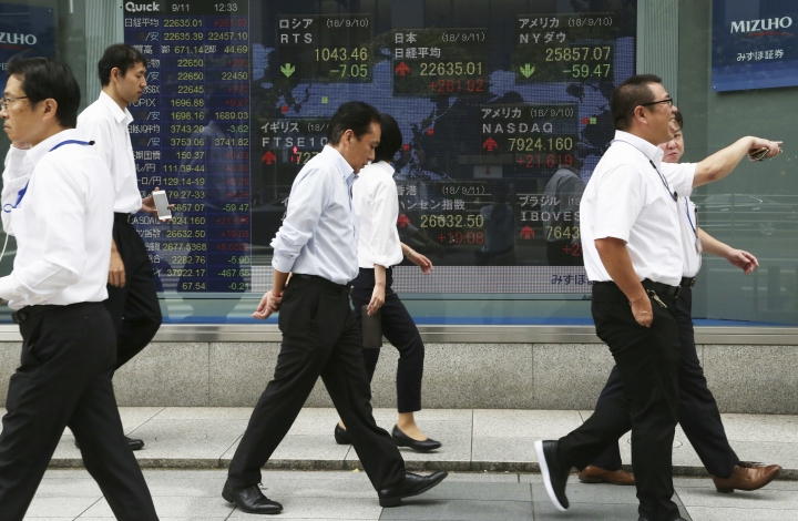 In this Sept. 11, 2018, photo, people walk by an electronic stock board of a securities firm in Tokyo. Shares have fallen in Asia after China rebuffed a plan for talks with the U.S. on resolving their dispute over trade and technology. Shares fell in Hong Kong, India and Australia, while markets in Japan, South Korea and elsewhere were closed Monday, Sept. 24, for national holidays. The slow start to the week followed a mixed close Friday on Wall Street, where an afternoon sell-off erased modest gains for the S&P 500 that had the benchmark index on track to eke out its own record high for much of the day.(AP Photo/Koji Sasahara)