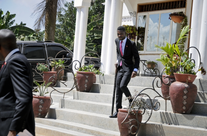 Pop star turned opposition lawmaker Bobi Wine, whose real name is Kyagulanyi Ssentamu, walks with the help of a cane to speak with the media at his house in Kampala, Uganda Monday, Sept. 24, 2018. Wine says he is concerned about his safety four days after returning home from the United States, where he sought medical care for injuries sustained during alleged state torture. (AP Photo/Ronald Kabuubi)